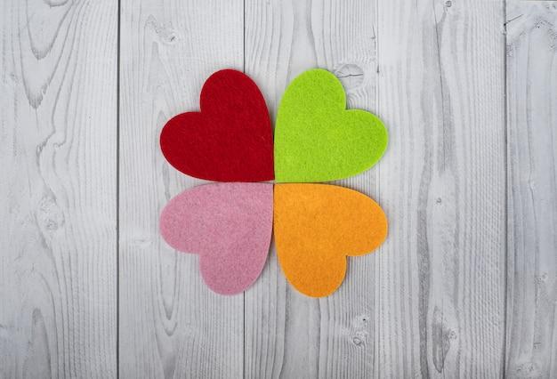 グレーと白の木製テーブルの上の4つの色の心。聖バレンタインの日の概念