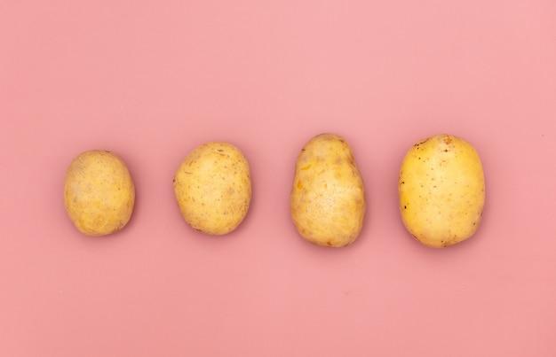 ピンクの背景の4つのジャガイモ