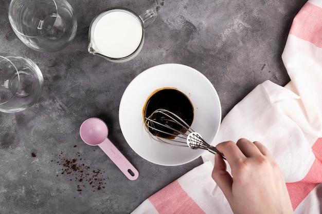 人気の韓国のダルゴンコーヒーを一歩ずつ調理します。ステップ4は、濃い灰色のスペースでボウルに泡立て器で可溶性コーヒー、砂糖、お湯を泡立て始めます。フラットレイ、トップビュー