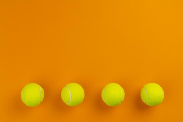 オレンジ色の背景の4つのテニスボール