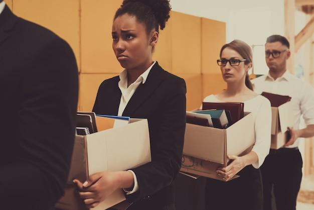 キューの4人のマネージャーが事務所の箱を抱えています。