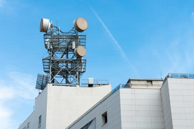 美しい青い空に屋外の建物の上にアンテナを持つ通信、電柱または通信塔。 4gまたは5g通信タワーアンテナの概念。