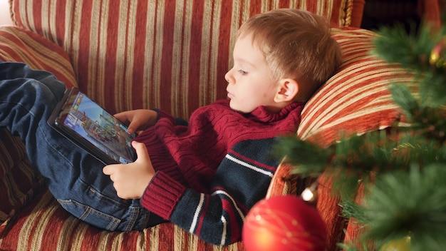 거실에서 안락의자에 누워 디지털 태블릿 컴퓨터에서 비디오 게임을 하는 어린 소년의 4k 클로즈업 영상. 겨울 방학과 축하 행사를 즐기는 아이.