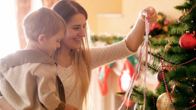 4k footage of happy smiling young woman with little son decorating christmas tree with garlands and ribbons. family preparing and decorating house on winter holidays and celebrations.