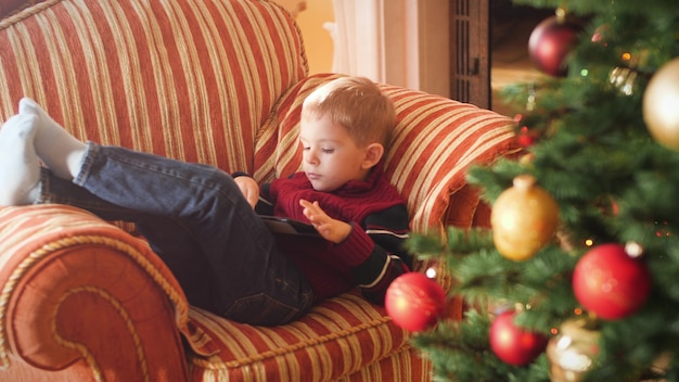 4k footage of little boy lying on sofa at living room and using tablet computer. child having fun on winter holidays and celebrations.