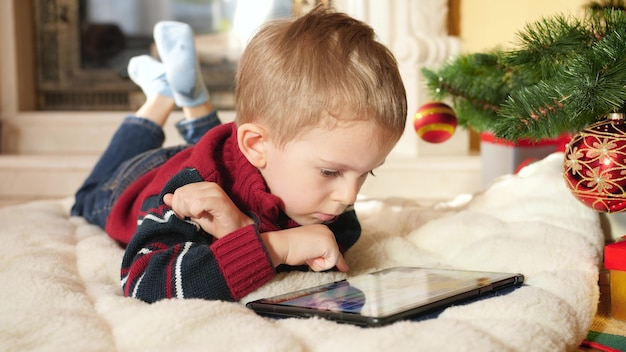 4k footage of little boy using and playing on digital computer while lying next to hristmas tree at house. child having fun on winter holidays and celebrations.