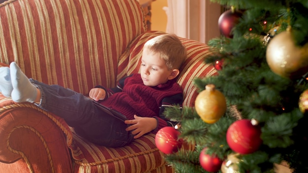 4k footage of little boy using tablet computer and browsing internet while lying on sofa next to christmas tree. child having fun on winter holidays and celebrations.