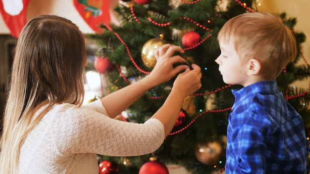 4k footage of little boy with mother decorating christmas tree in living room. family decorating house on winter holidays and celebrations.