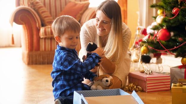 4k кадры, на которых симпатичный маленький мальчик и его мать упаковывают игрушки в подарочные коробки, чтобы дарить подарки на рождество. семья дарит и получает подарки на зимние праздники и торжества.