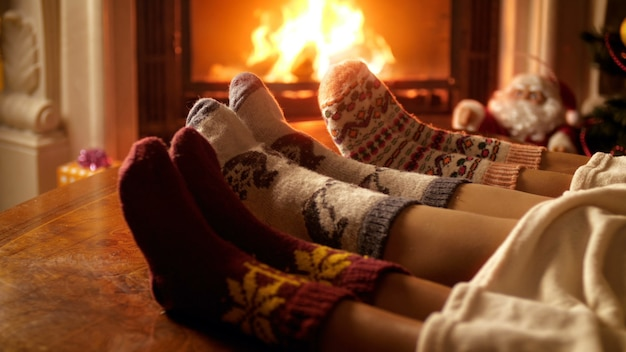4k кадры семьи в теплых шерстяных носках с предупреждением у горящего камина в канун рождества. люди отдыхают на зимних праздниках и праздниках дома