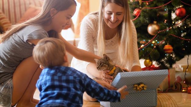 4k кадры счастливой семьи, открывающей рождественские подарки и подарки. милый котенок выходит из коробки. семья весело и весело провести время на зимних праздниках и торжествах.