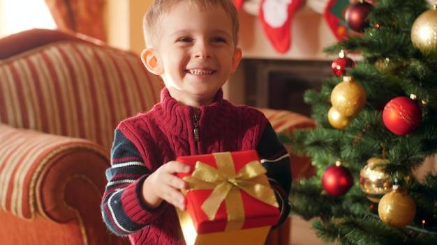 4k кадры счастливого улыбающегося маленького мальчика, держащего рождественский подарок в коробке и показывающего его подарок в камере. ребенок получает подарки и подарки от санта-клауса на зимние праздники и торжества