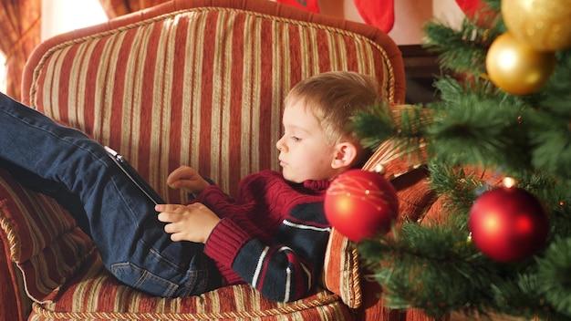 크리스마스 아침에 안락의자에 누워 디지털 태블릿으로 게임을 하는 어린 소년의 4k 영상