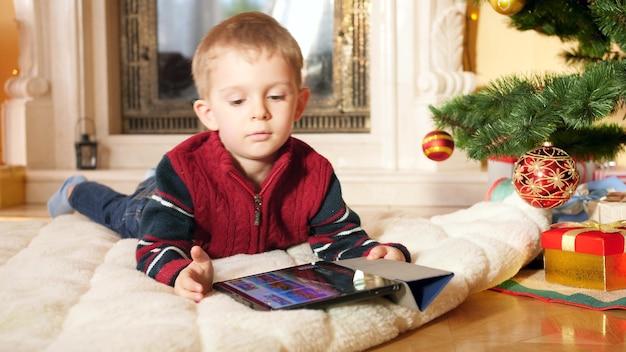크리스마스 트리 아래 담요에 누워 디지털 태블릿 컴퓨터에서 비디오 게임을 하는 어린 소년의 4k 영상. 겨울 방학과 축하 행사를 즐기는 아이.
