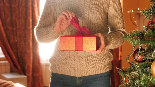 4k кадры молодой женщины, развязывающей красную ленту и открывающей коробку с рождественским подарком утром
