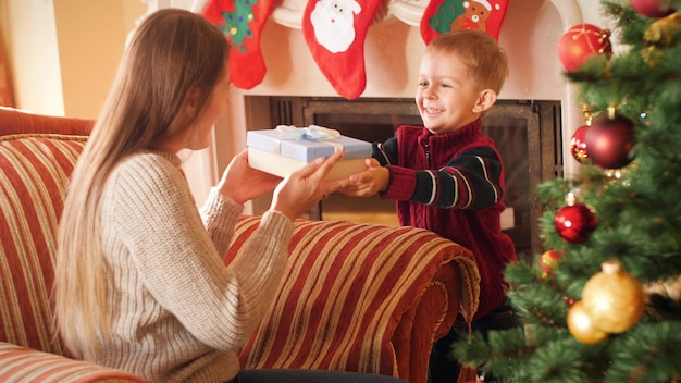 4k footage of smiling little boy giving christmas present to his mother. family giving and receiving new year presents in living room next to christmas tree.
