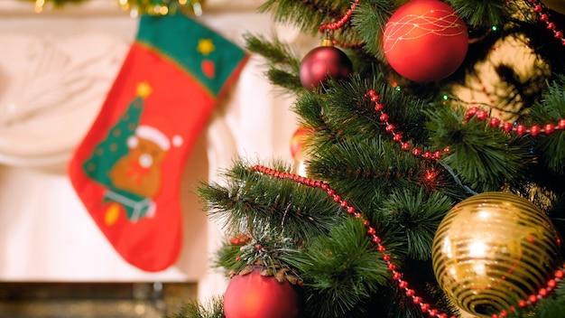 プレゼント用の吊り下げ式ソックスとカラフルな花輪、ビーズ、つまらないものがたくさんあるクリスマスツリーを備えた装飾された暖炉の4kパン映像。冬のお祝いや休日にぴったりのショット