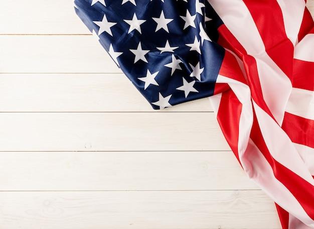 7 月 4 日、アメリカの独立記念日。白い木製の背景にアメリカ国旗のトップ ビュー、フラット レイアウト トップ ビュー、コピー スペース