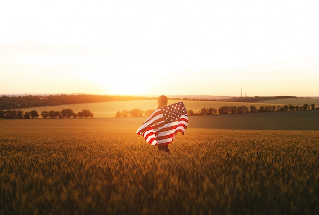 4th of july.  woman with the american flag running in a wheat field at sunset.  independence day, patriotic holiday.