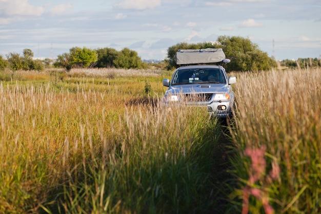 秋の高い草のある牧草地で4x4車