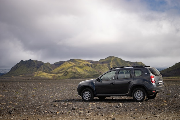 4x4 car parked off road on the black lava field on the way to landmannalaugar area, iceland.