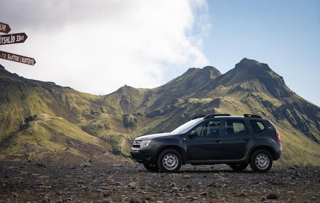 Автомобиль 4х4 припаркован у дороги на черном лавовом поле по дороге в район ландманналаугар, исландия.