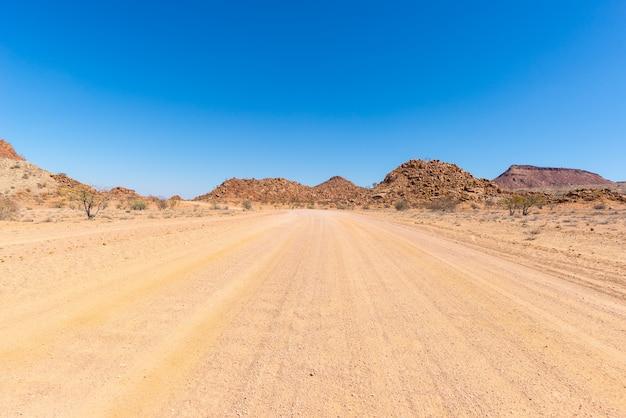 Дорога гравия 4x4 пересекая красочную пустыню на twyfelfontein, в величественном damaraland brandberg, намибия, африка.