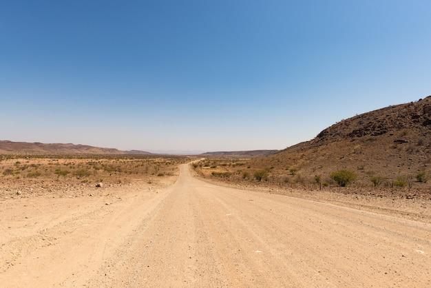 Дорога гравия 4x4 пересекая красочную пустыню на twyfelfontein, в величественном damaraland brandberg, сценарное назначение перемещения в намибии, африке.