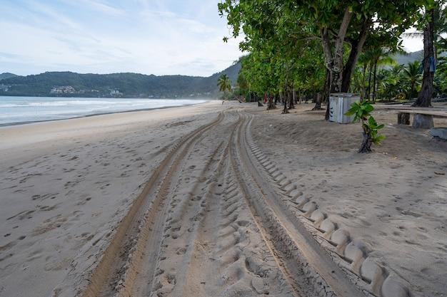 4 x 4 타이어 트랙 십자형 타이어는 patong 해변 phuket thailand의 모래 질감 배경에서 추적합니다.