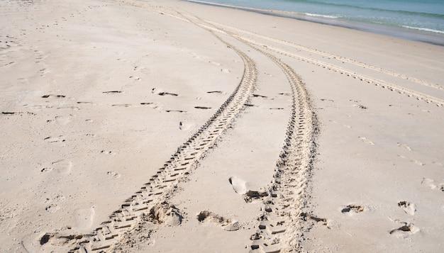 砂のテクスチャの背景に交差する4x4タイヤトラック。