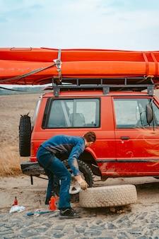 男は新しい交換用ホイールをロードトラックから4x4に転がす