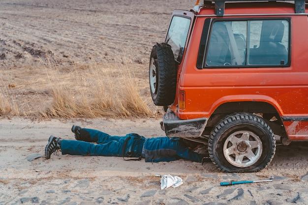 未舗装の道路で4x4車の下に横たわる男