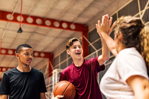 お互いに高い5を与えるバスケットボールコートで10代の友人のグループ