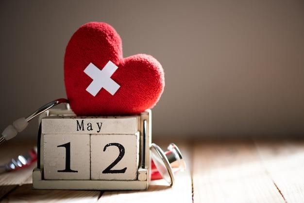 国際看護師の日、5月12日。木の背景に聴診器を持つ赤い心。
