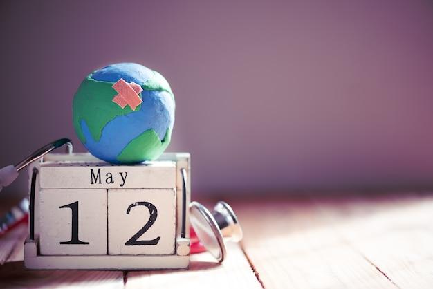 国際看護師の日、5月12日。木製テーブルのバックグラウンドに聴診器を持つ手作りの地球儀
