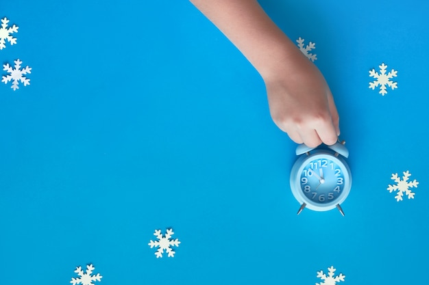 紙雪片で5〜12を示す青い目覚まし時計を持っている子供の手