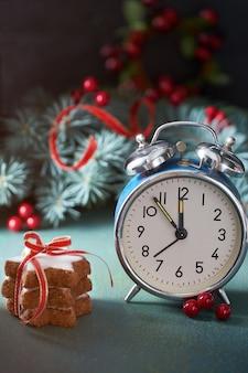 クリスマスのモミの小枝、赤い果実、スタークッキー、青いヴィンテージの目覚まし時計を5から12に設定。
