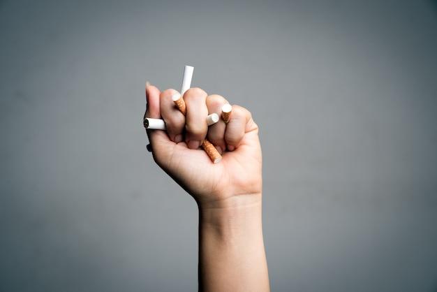 世界のたばこの日、5月31日。喫煙をやめます。男の手がタバコを粉砕
