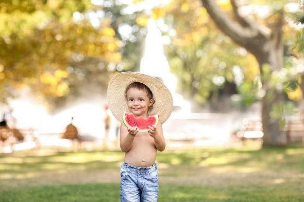 スイカのスライスを食べるシャツを着ていないショートパンツの緑の芝生で5〜6歳の少年