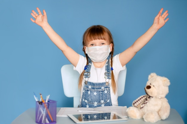 Девочка 5-6 лет, сидя за столом, выполняет домашнее задание по удаленным заданиям на планшете. изолировать на синей стене. коронавирус, замаскированный ребенок.