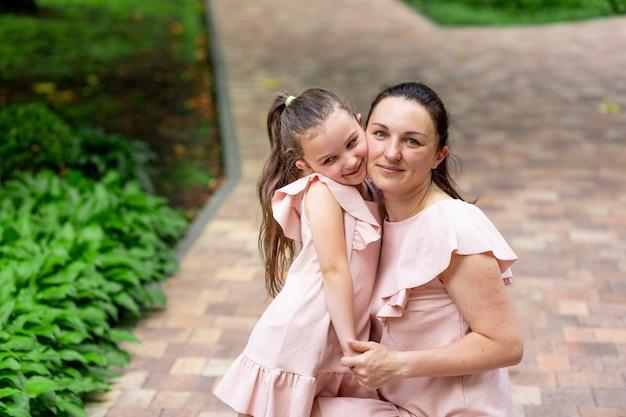 Счастливая мама и дочь 5-6 лет гуляют в парке летом, мама обнимает дочь, концепция счастливой семьи, отношения матери и ребенка, день матери