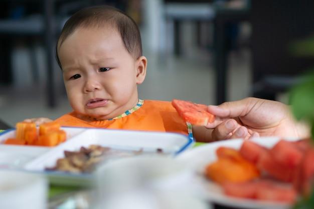 かわいい5-6ヶ月のアジアの女の赤ちゃんはスイカを食べたくない