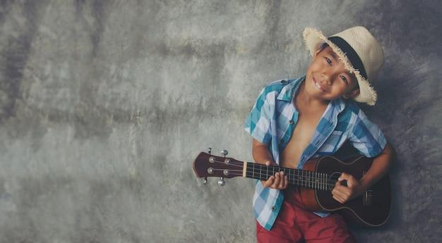 アジアの少年5-6歳プレイウクレレクールなジェスチャー音楽空きスペースで情熱的な愛