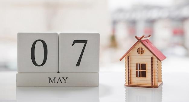 5月のカレンダーとおもちゃの家。月の7日目。印刷または記憶用のカードメッセージ