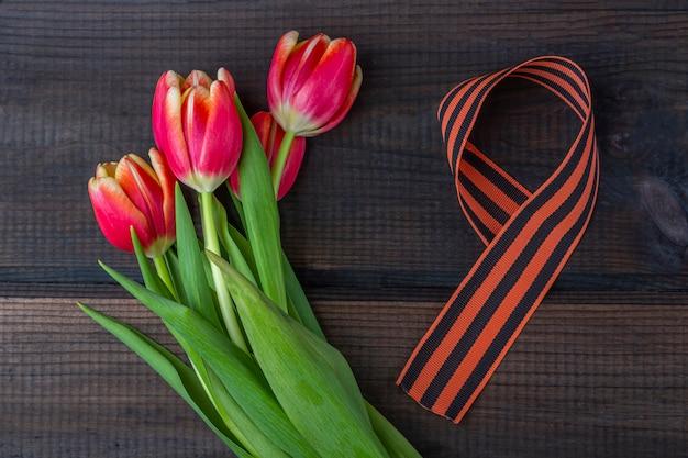 5月9日背景-赤いチューリップ、木製の背景にジョージのリボン。戦勝記念日または祖国の擁護者の日の概念。トップビュー、テキストのコピースペース