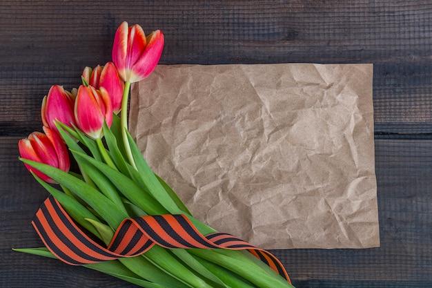 5月9日の背景-赤いチューリップ、ジョージのリボン、木製の背景に紙のノートとテンプレート空白のグリーティングカード。戦勝記念日または祖国の擁護者の日の概念。トップビュー、テキストのコピースペース