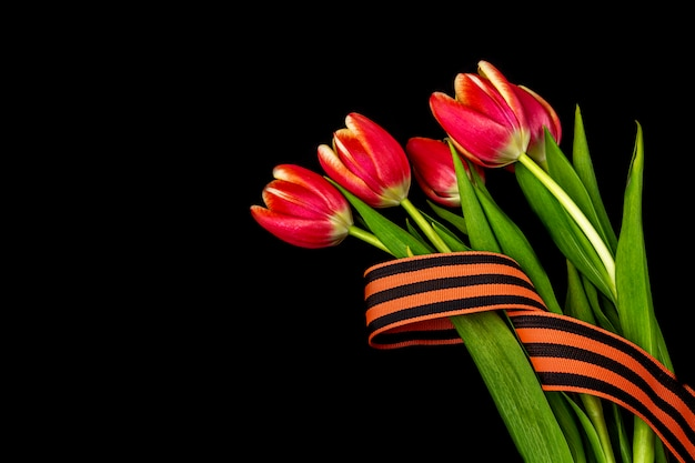 5月9日まで空白のグリーティングカード。赤い花、黒いノートにジョージのリボン。戦勝記念日または祖国の擁護者の日の概念。トップビュー、テキストのコピースペース