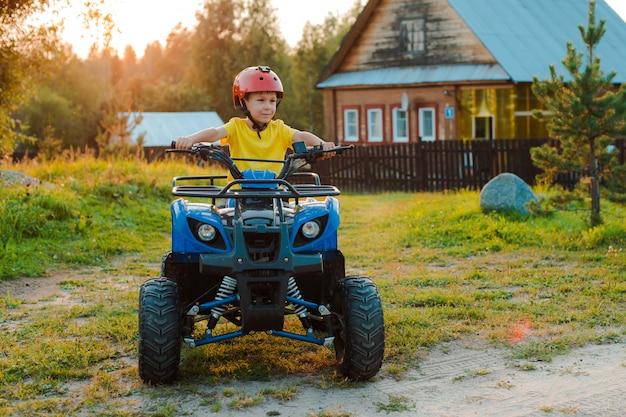 小さな男の子5歳の子供のatvは、夏の休暇の夕日の村の家に乗ります。クワッドバイク