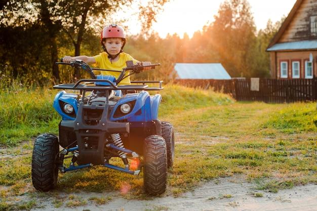 小さな男の子5歳の子供のatvは夏休みに村の家に乗る