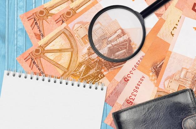 Купюры 5 белорусских рублей и увеличительное стекло с черным кошельком и блокнотом. понятие о поддельных деньгах. поиск различий в деталях денежных купюр для обнаружения фальшивых денег